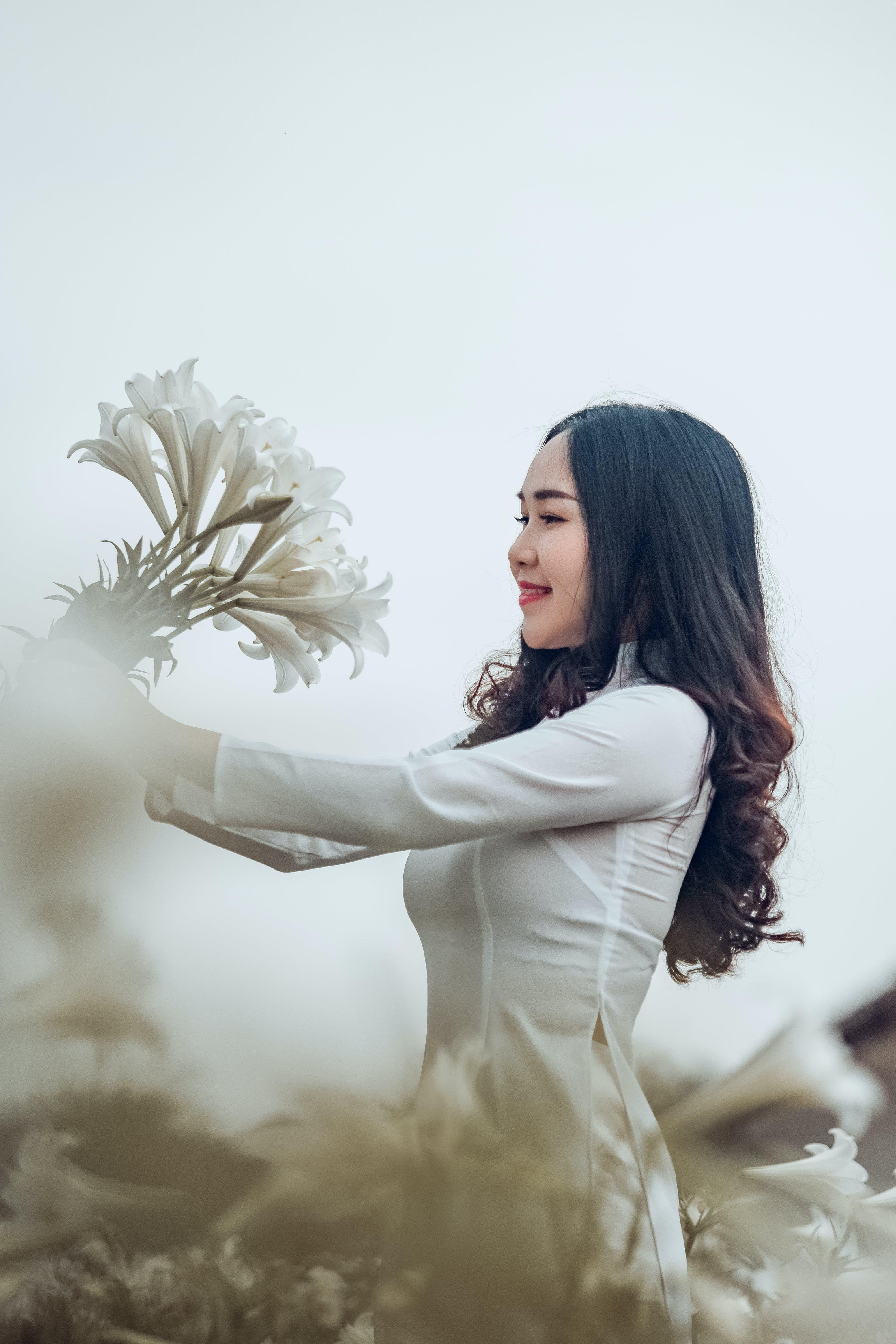 Woman Wearing White Shirt While Holding Flowers