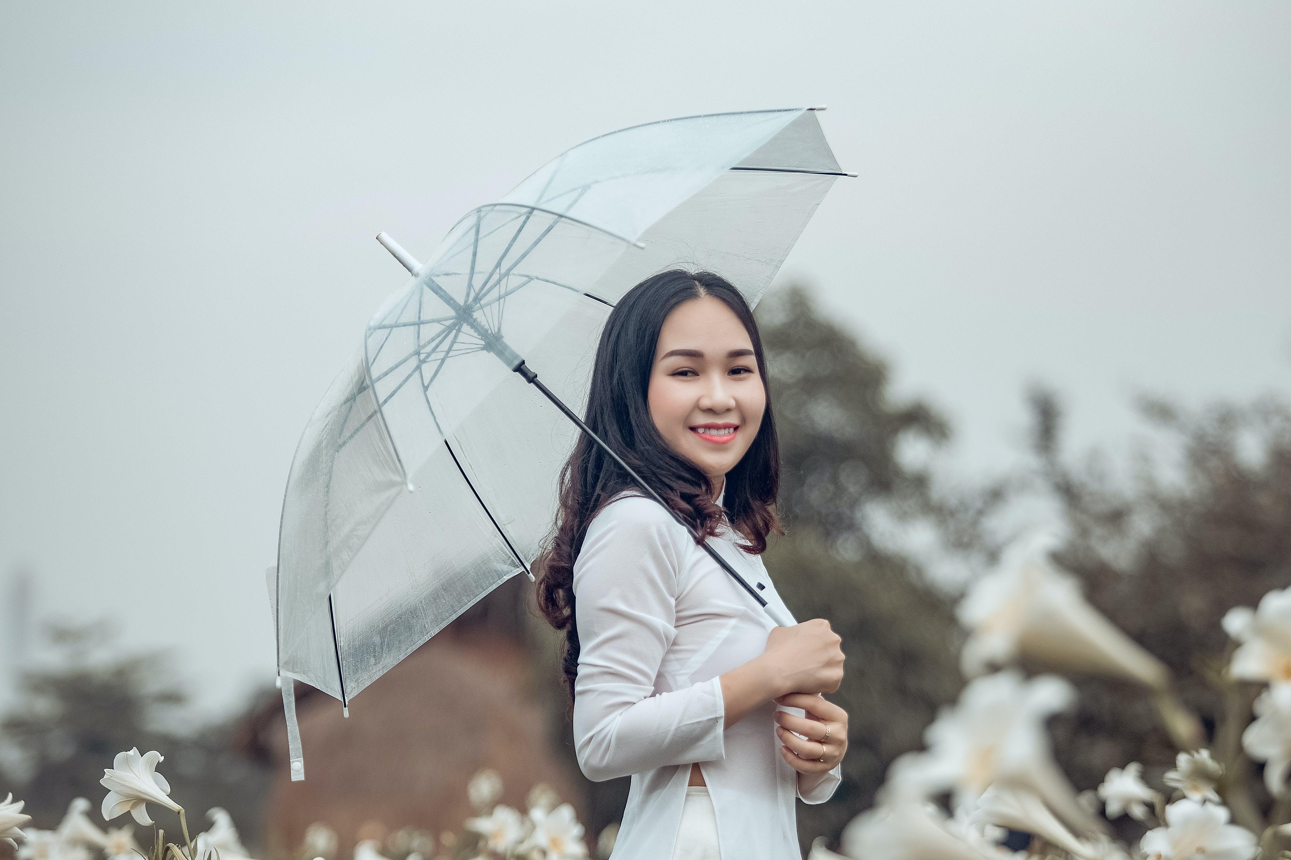 Woman Wearing White Long-sleeved Shirt While Holding Umbrella