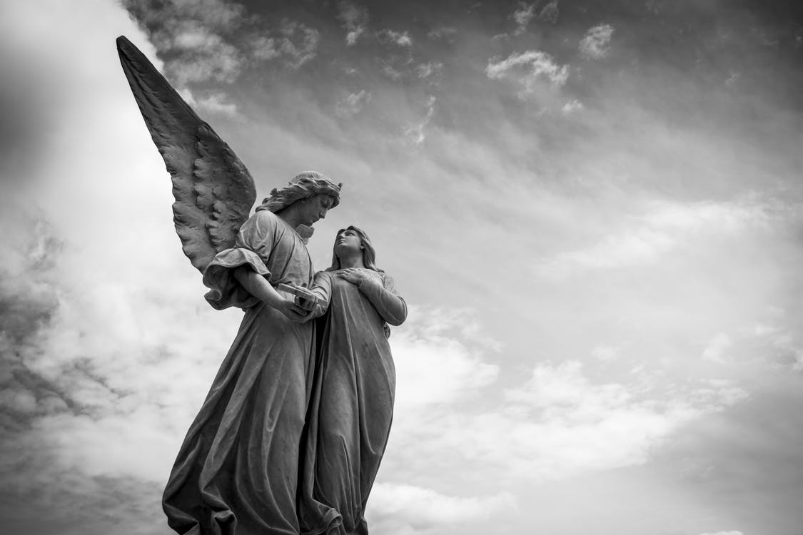 Grayscale Photography of Angel Statue Under Cloudy Skies