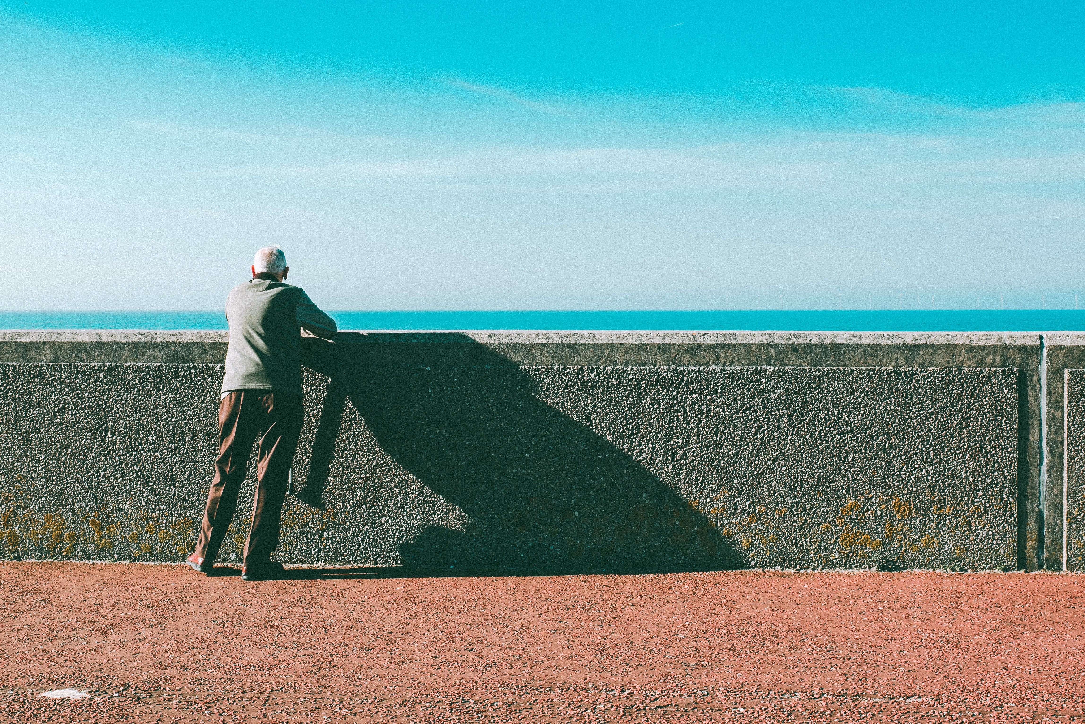 Man Leaning on Gray Concrete Wall Under Blue Sky