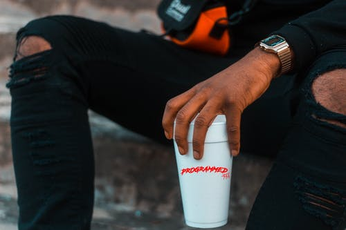 Man Holding Disposable Drinking Cup on Left Hand
