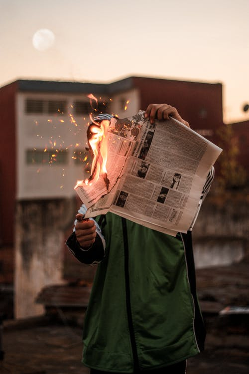 Person in Green Jacket Burning Newspaper