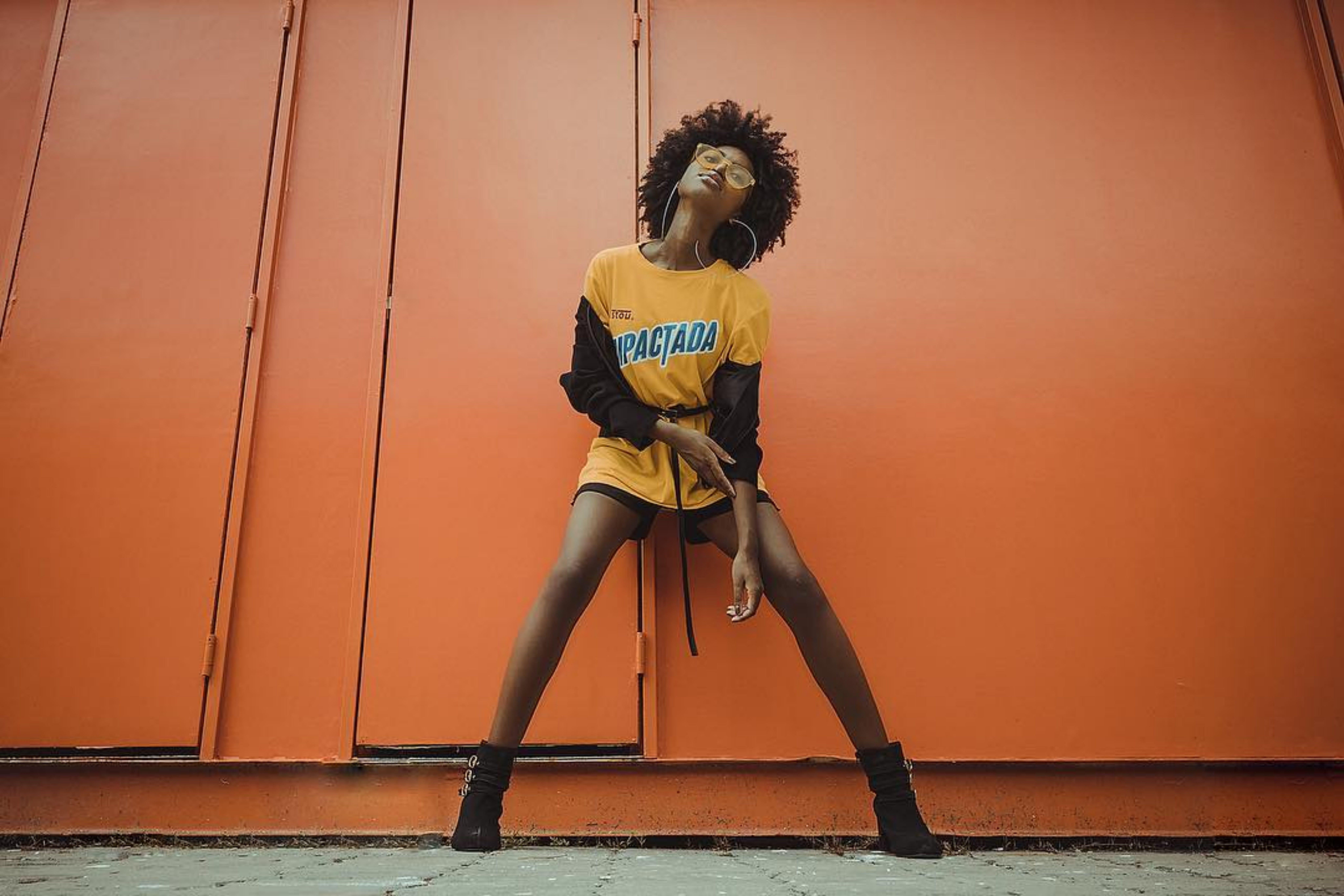 Woman in Yellow Shirt Standing Beside Orange Wall