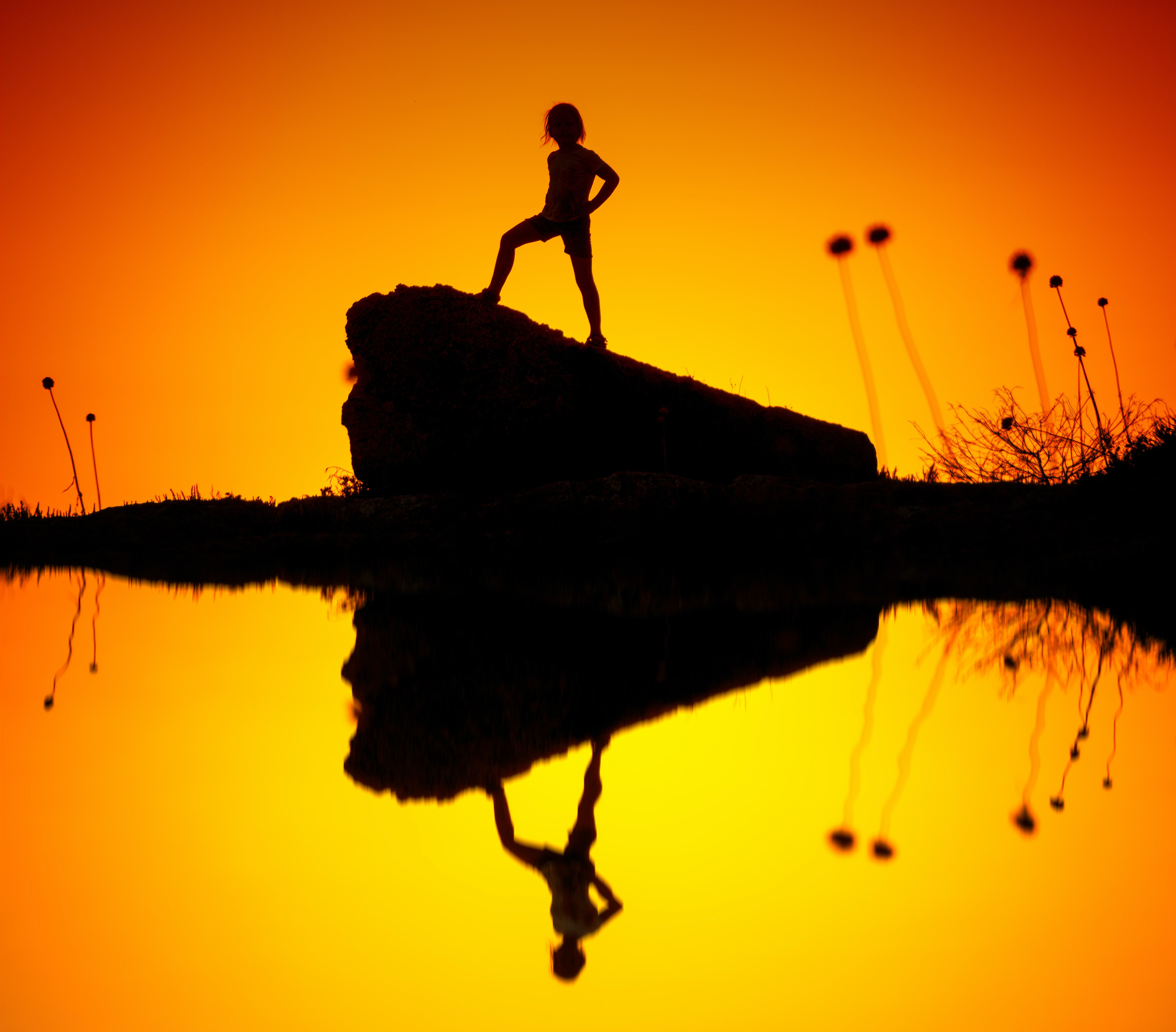Silhouette of Child Standing on Rock