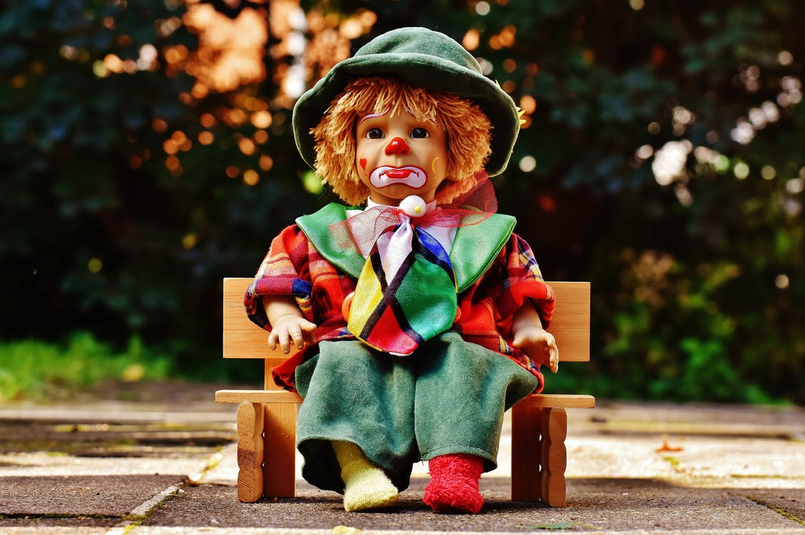 Clown Doll Sitting on Bench