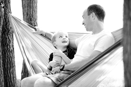 Grayscale Photo of Man and Child Sitting on Hammock