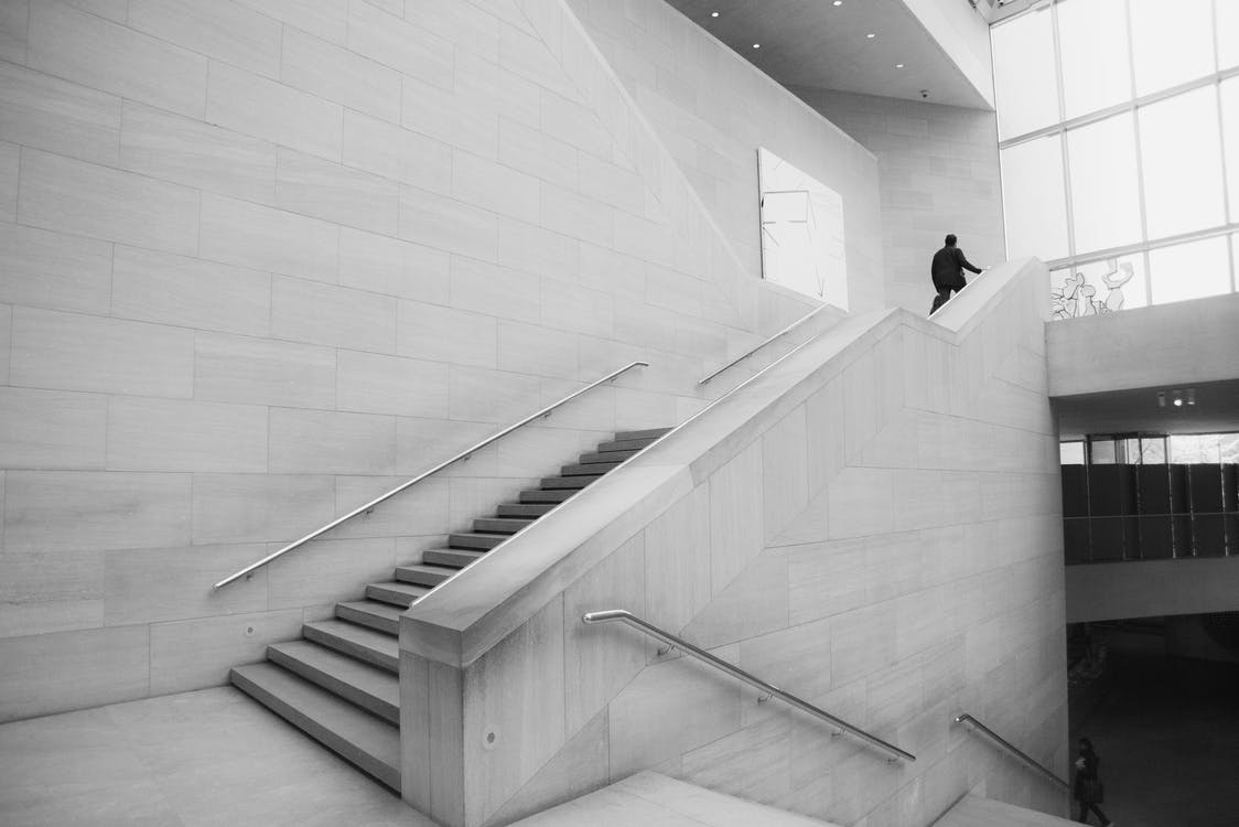 Person Walking Up Stairs Grayscale Photo