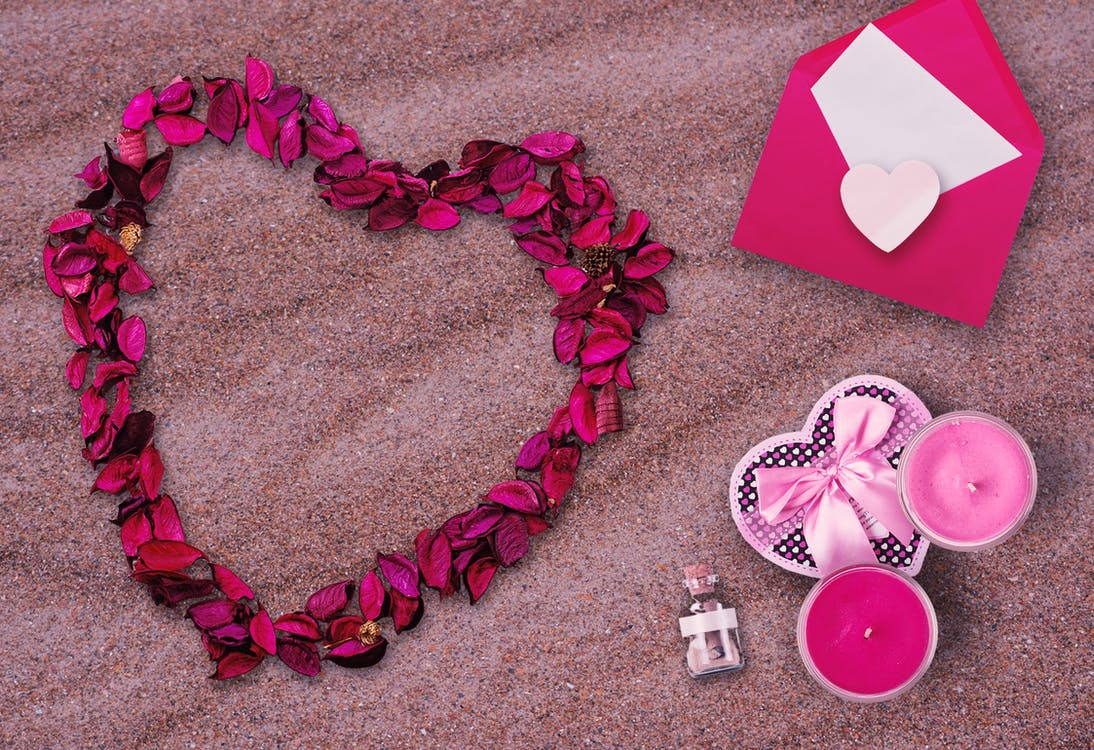 Pink Flower Petals and Pink Envelop on Top of Sand
