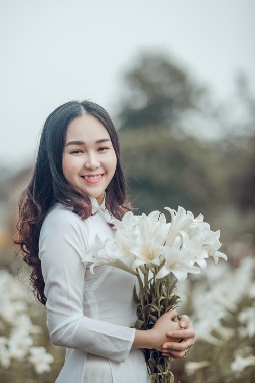 Photo of Smiling Woman Holding a Bouquet of White Flowers