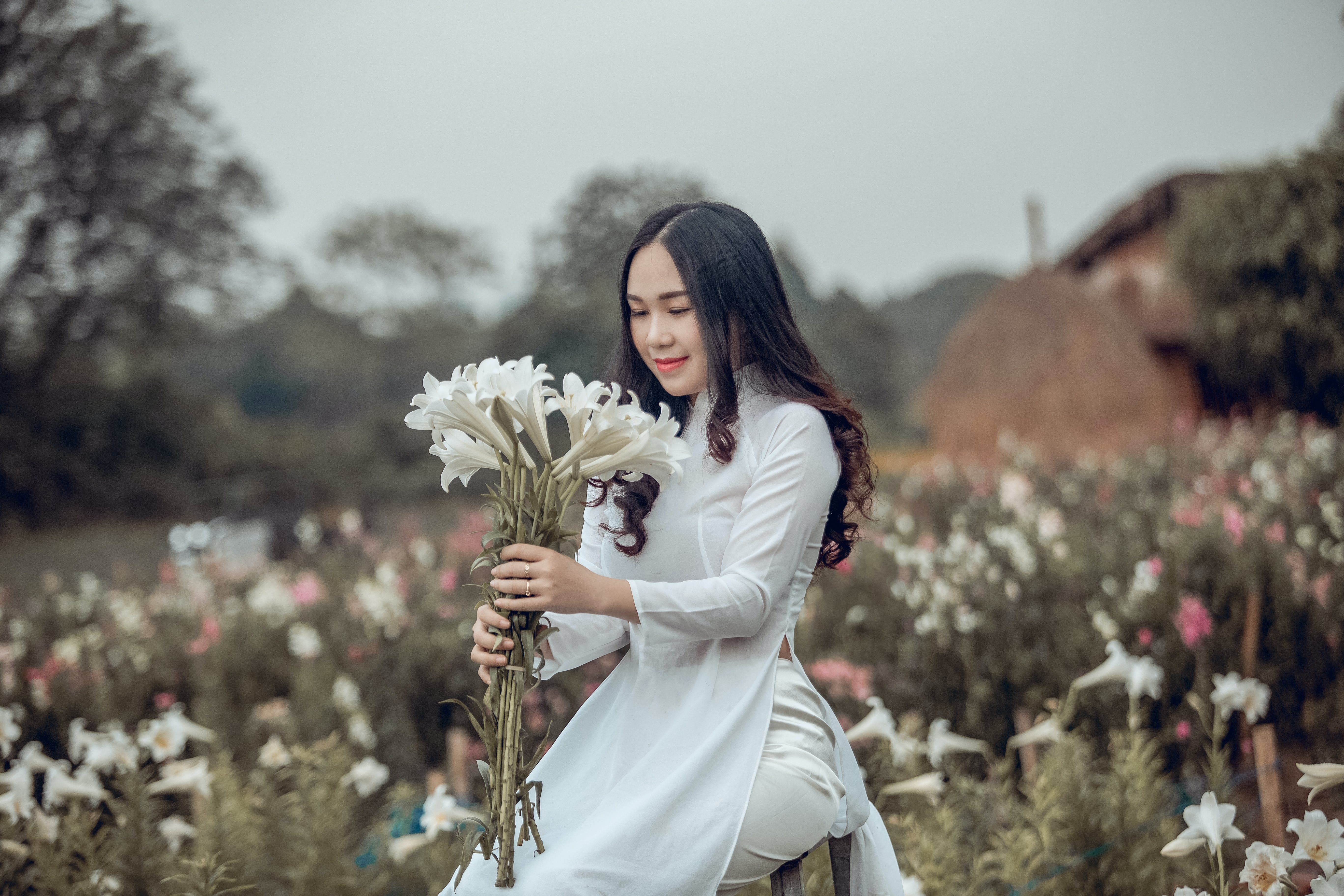 Photo of Woman In a White Outfit Kneeling While Holding White Petaled Flowers