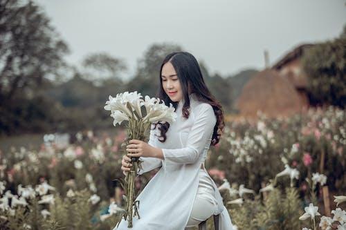 Foto profissional grátis de ajoelhado, bonita, branco, buquê de flores