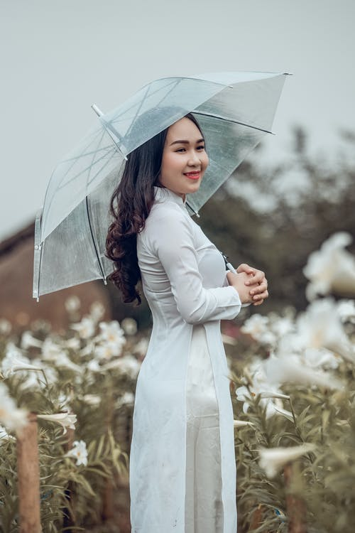 Woman in White Dress Holding Umbrella