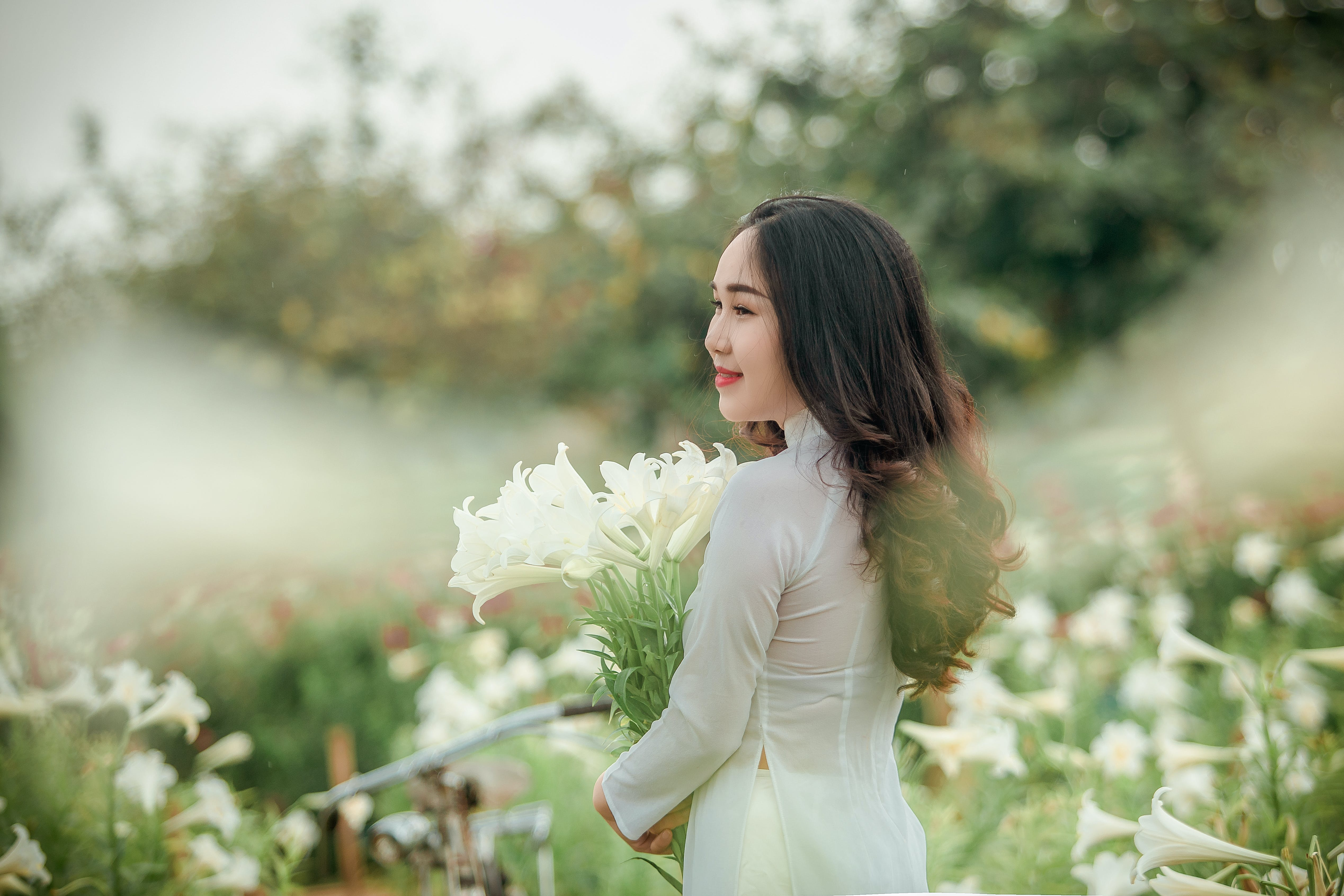 Woman in White Long-sleeved Dress Holding Flowers on Selective Focus Photography