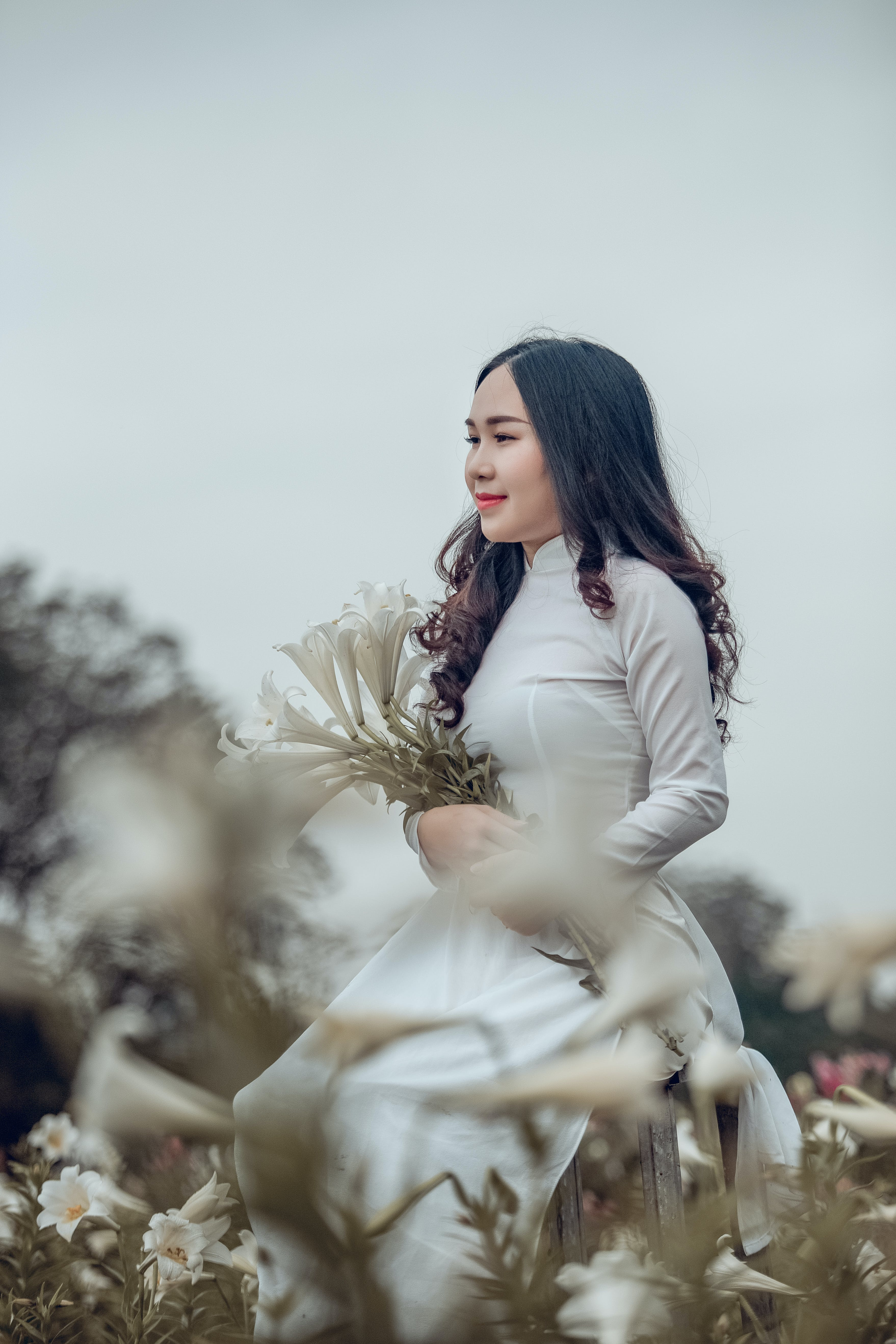 Woman Wearing White Turtleneck Long-sleeved Dress Holding Withe Petaled Flowers