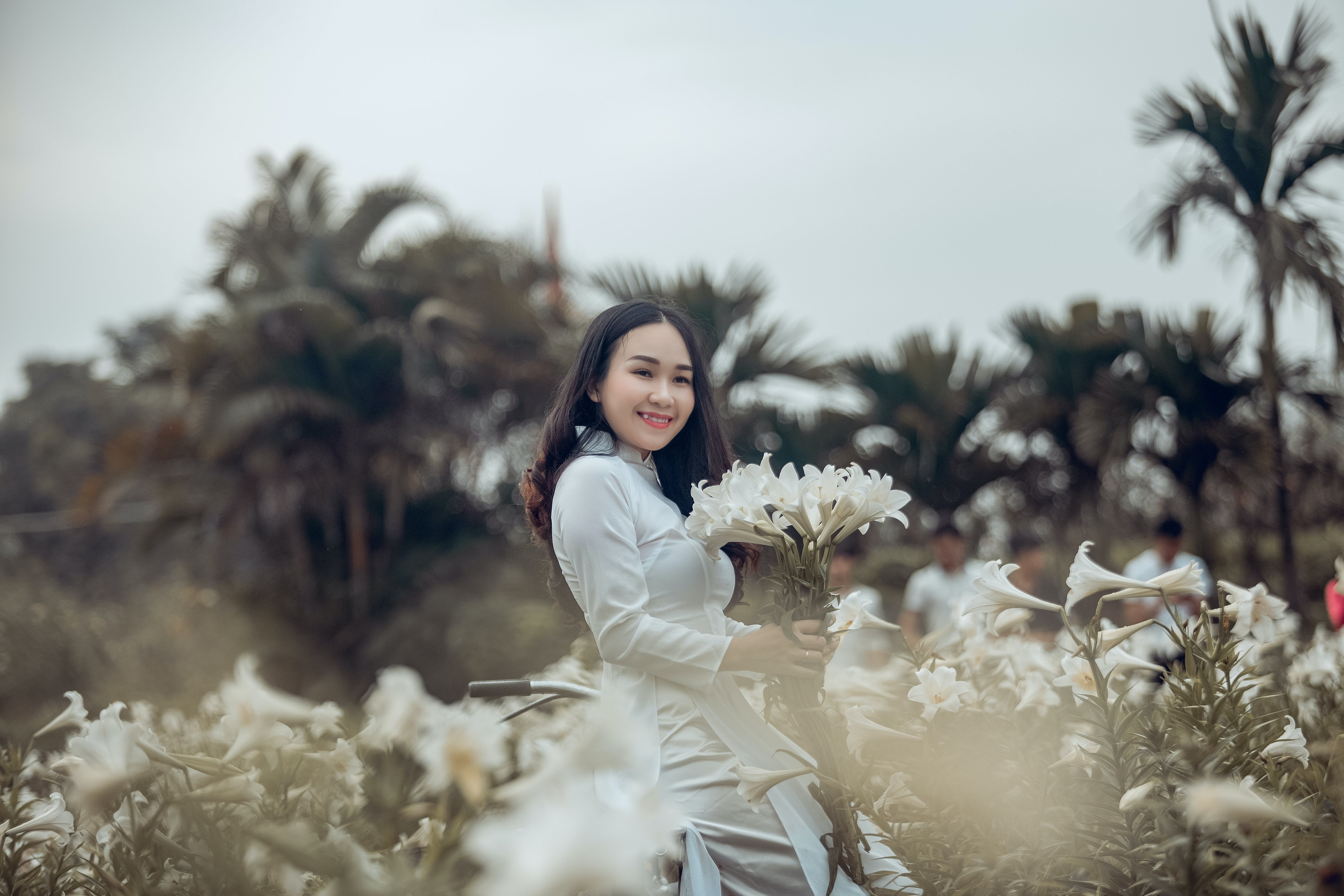 Woman in White Dress Standing and Holding White Petaled Flower and Smiling