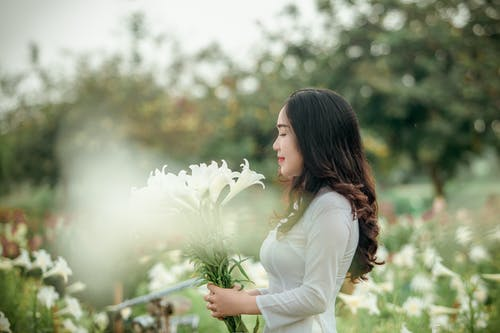 Woman in White Long-sleeved Dress Holding White Flowers on Selective Focus Photography