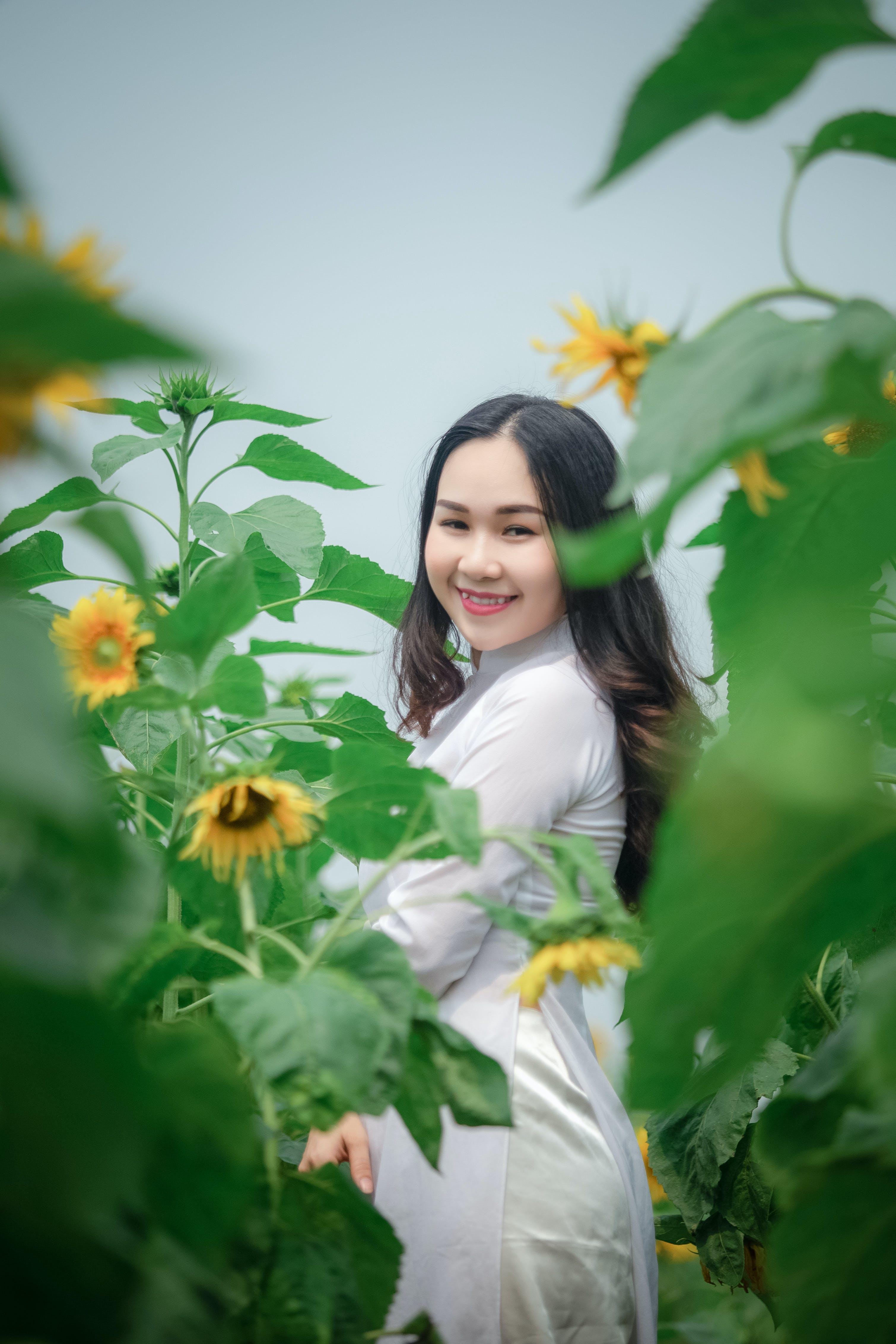 Woman in White Dress Standing on Sunflower Field
