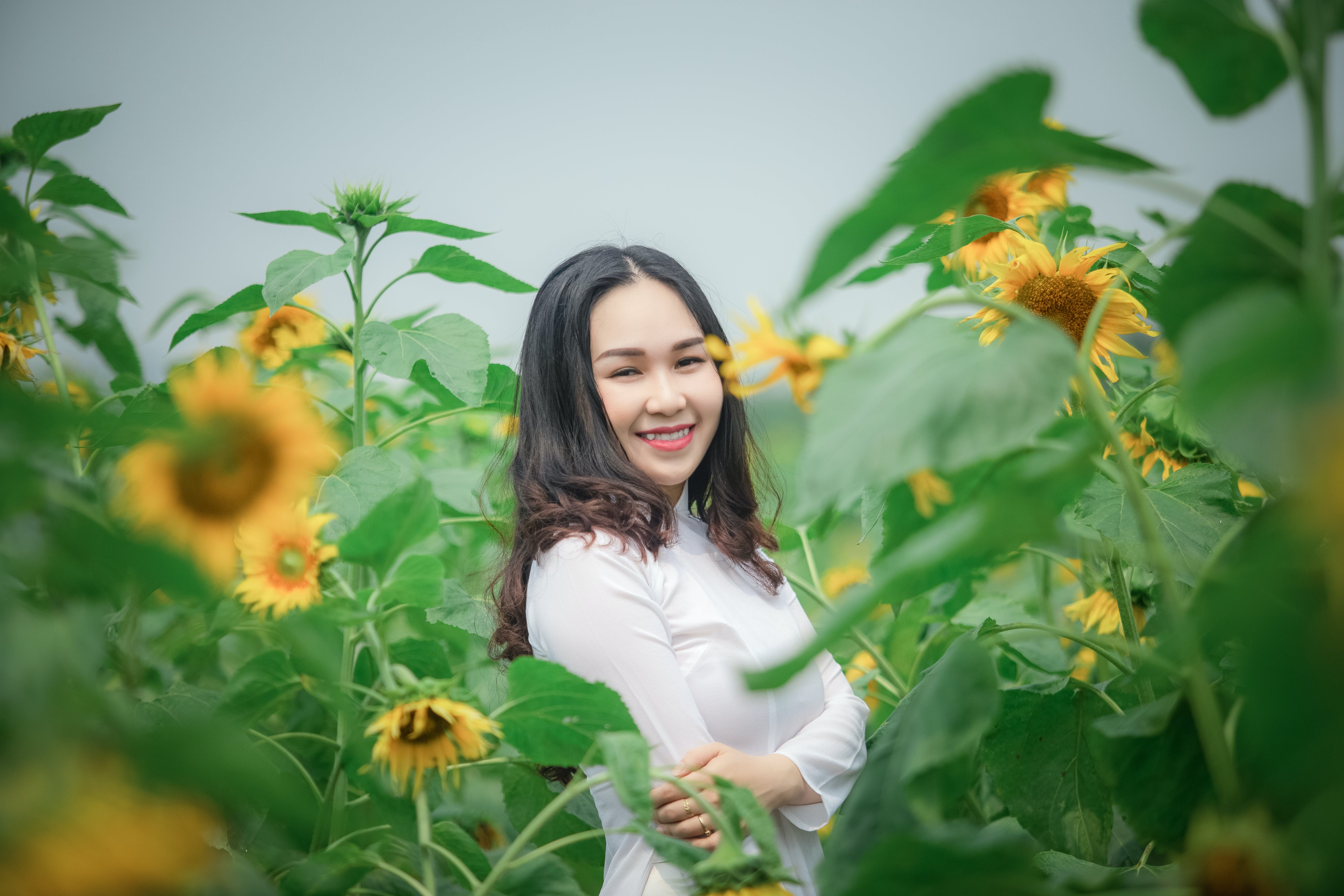 Woman Wearing White Shirt Standing Near Sunflower Field While Smiling