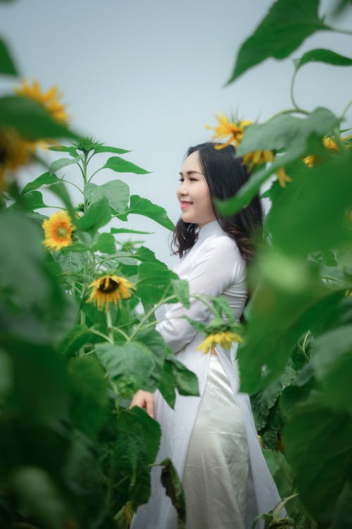 Woman in White Dress Standing on Sunflower Field