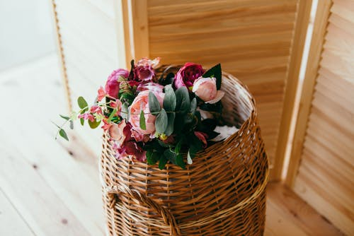 Round Brown Wicker Basket Filled With Pink and Red Flower