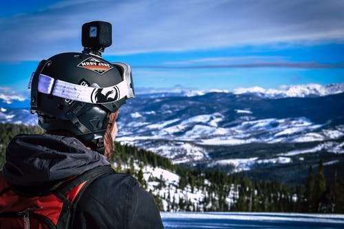 Man in Helmet With Action Camera Looking at Snow Mountain
