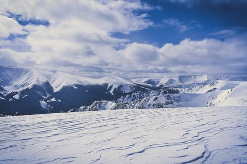 Snow Covered Hills Under White Clouds
