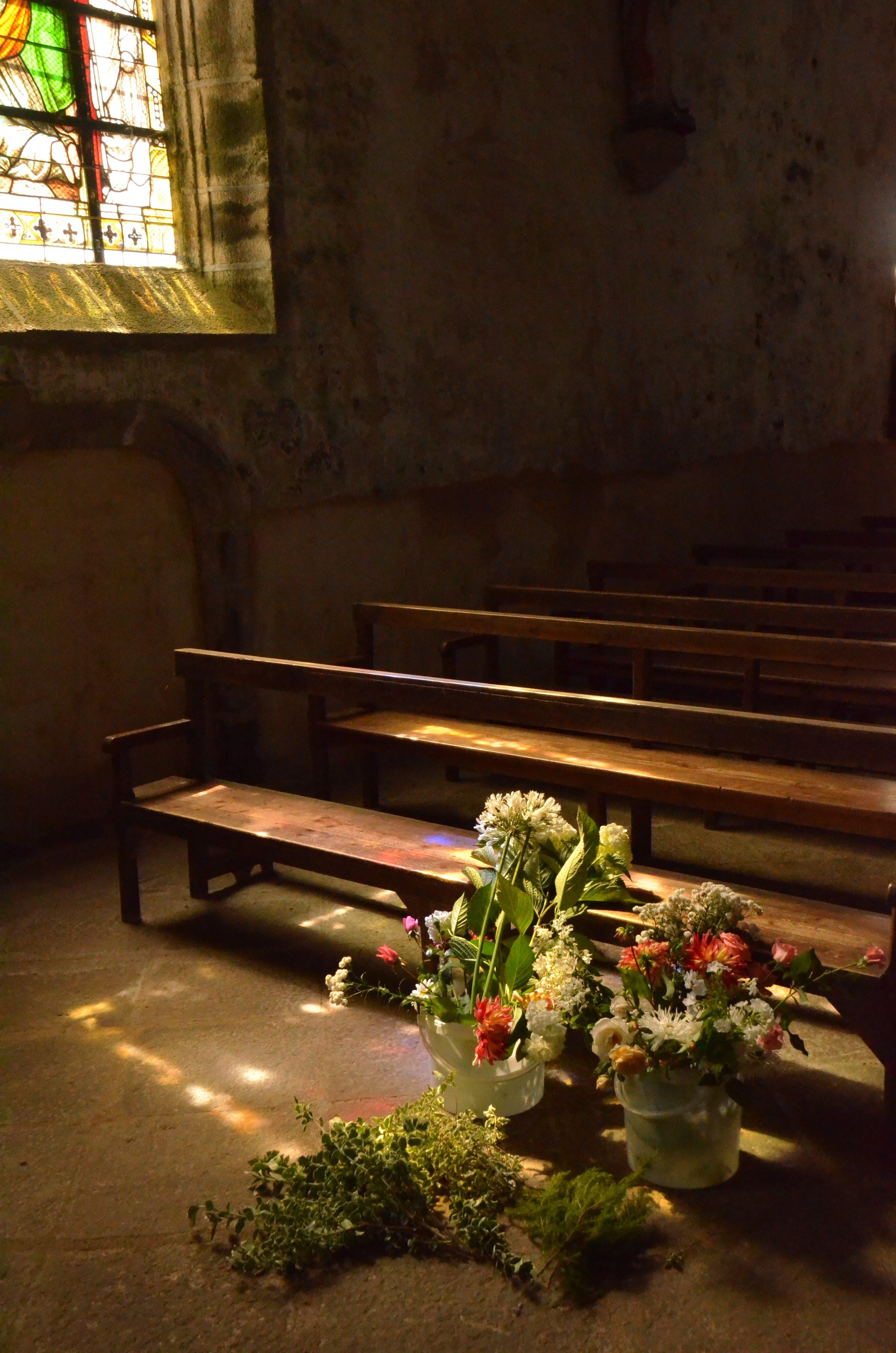 Flowers Placed Beside Brown Wooden Pew Inside Chapel