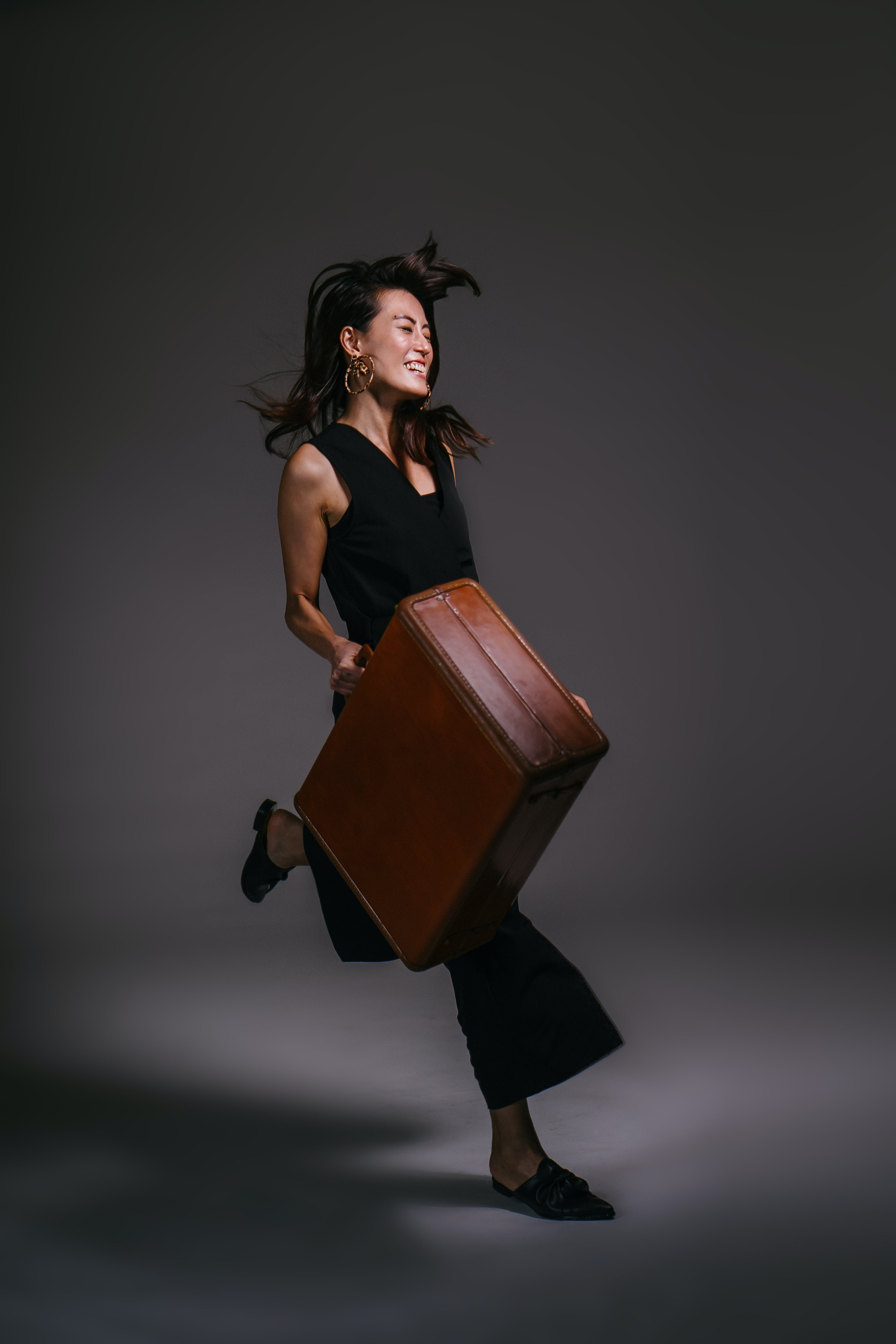 Photo of Smiling Woman Running While Holding Brown Leather Suit Case