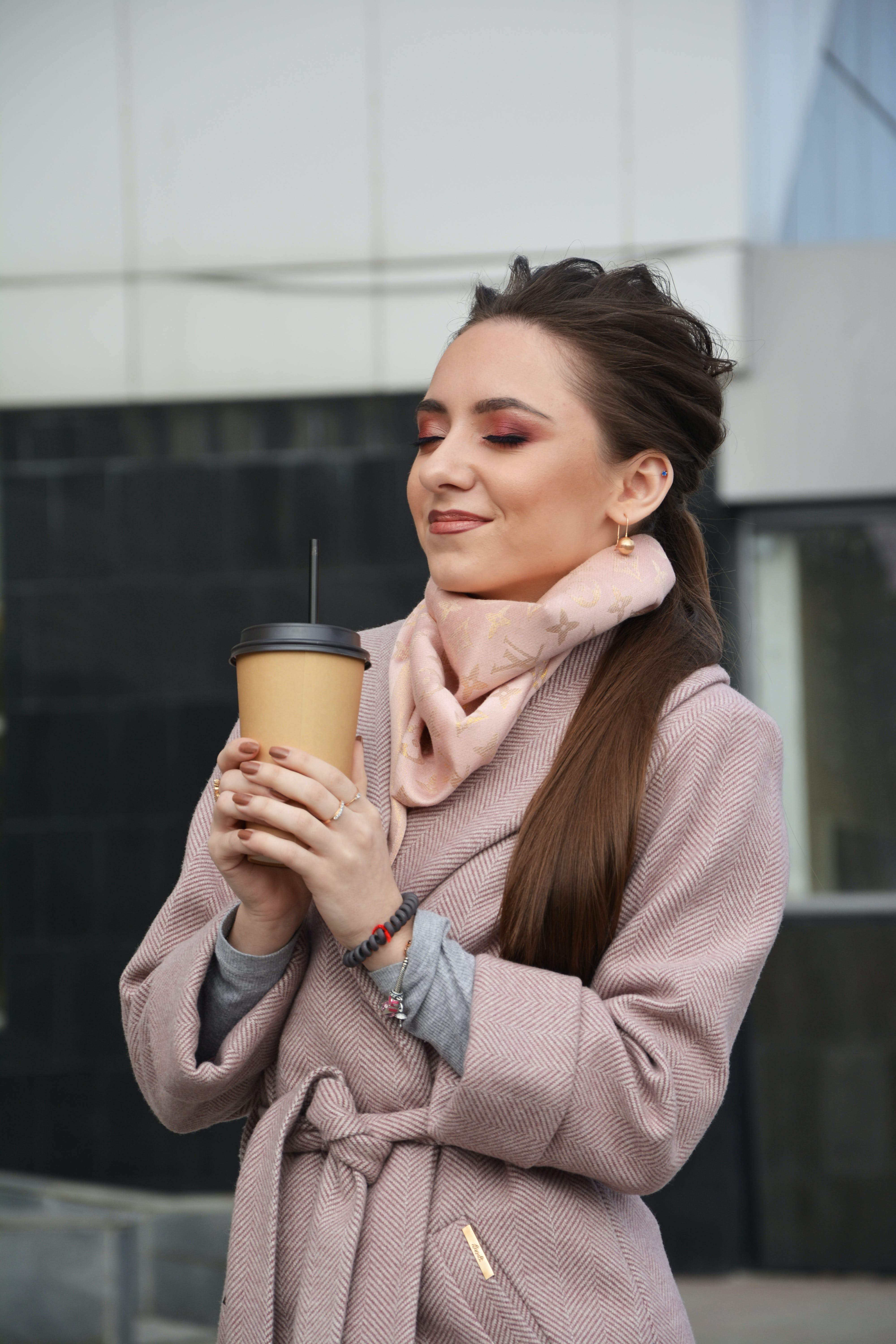 Photo of Woman With Her Eyes Closed Standing Holding a Plastic To Go Cup