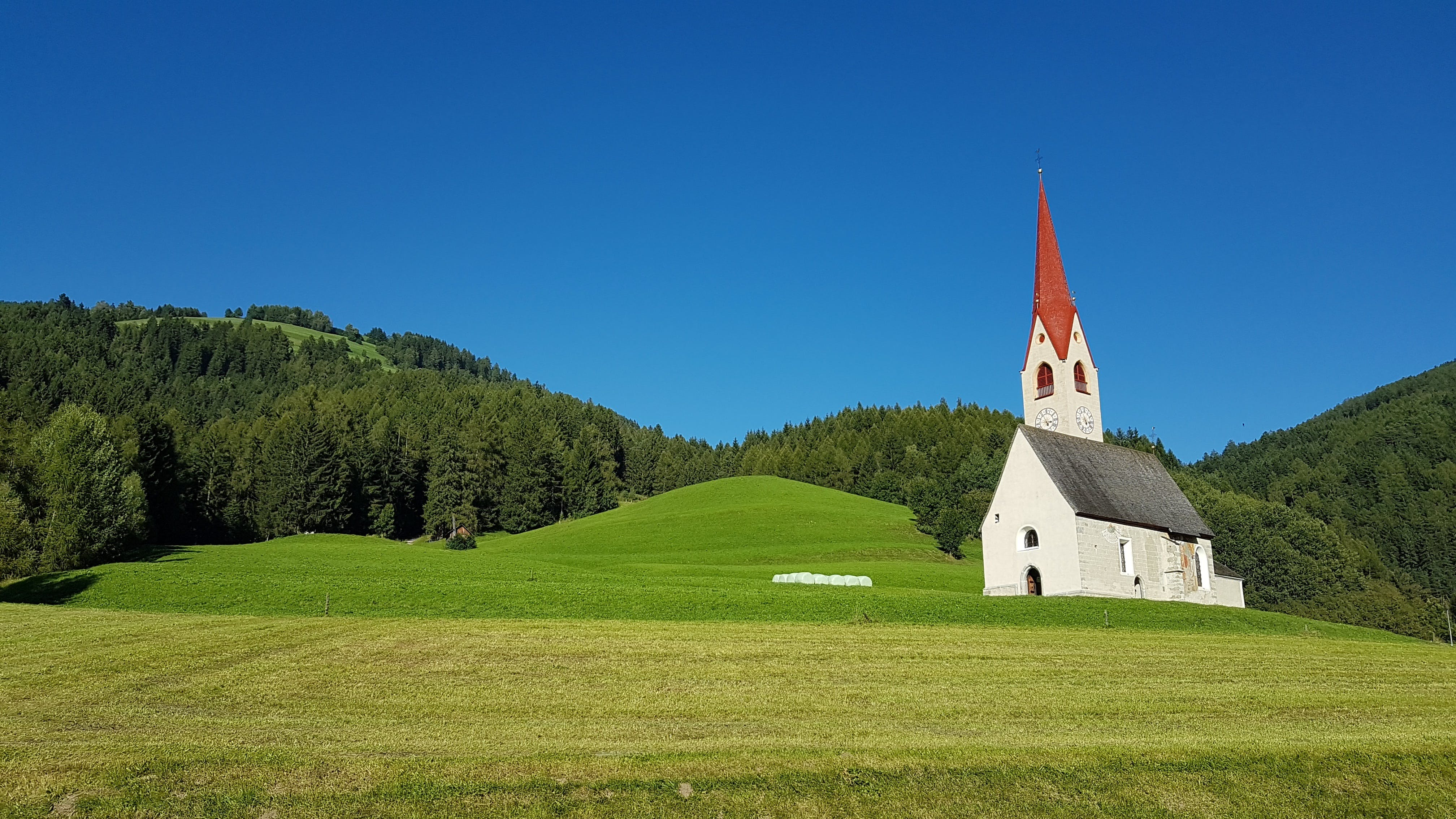 White Gray and Red Chapel on Green Field during Clear Sky Day Time