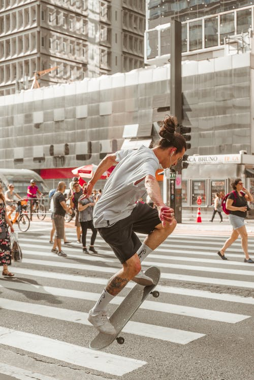 Photo of Man Riding Skateboard on Pedestrian