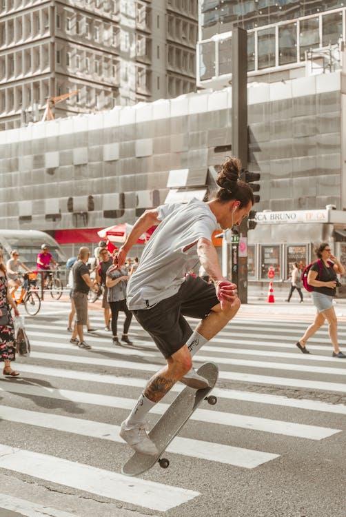 歩行者のスケートボードに乗る男の写真