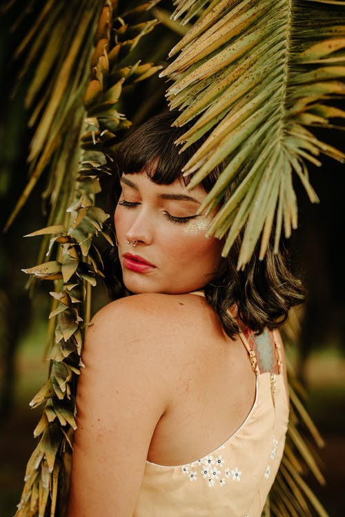 Photo of Woman Standing Under Palm Leafs With Her Eyes Closed