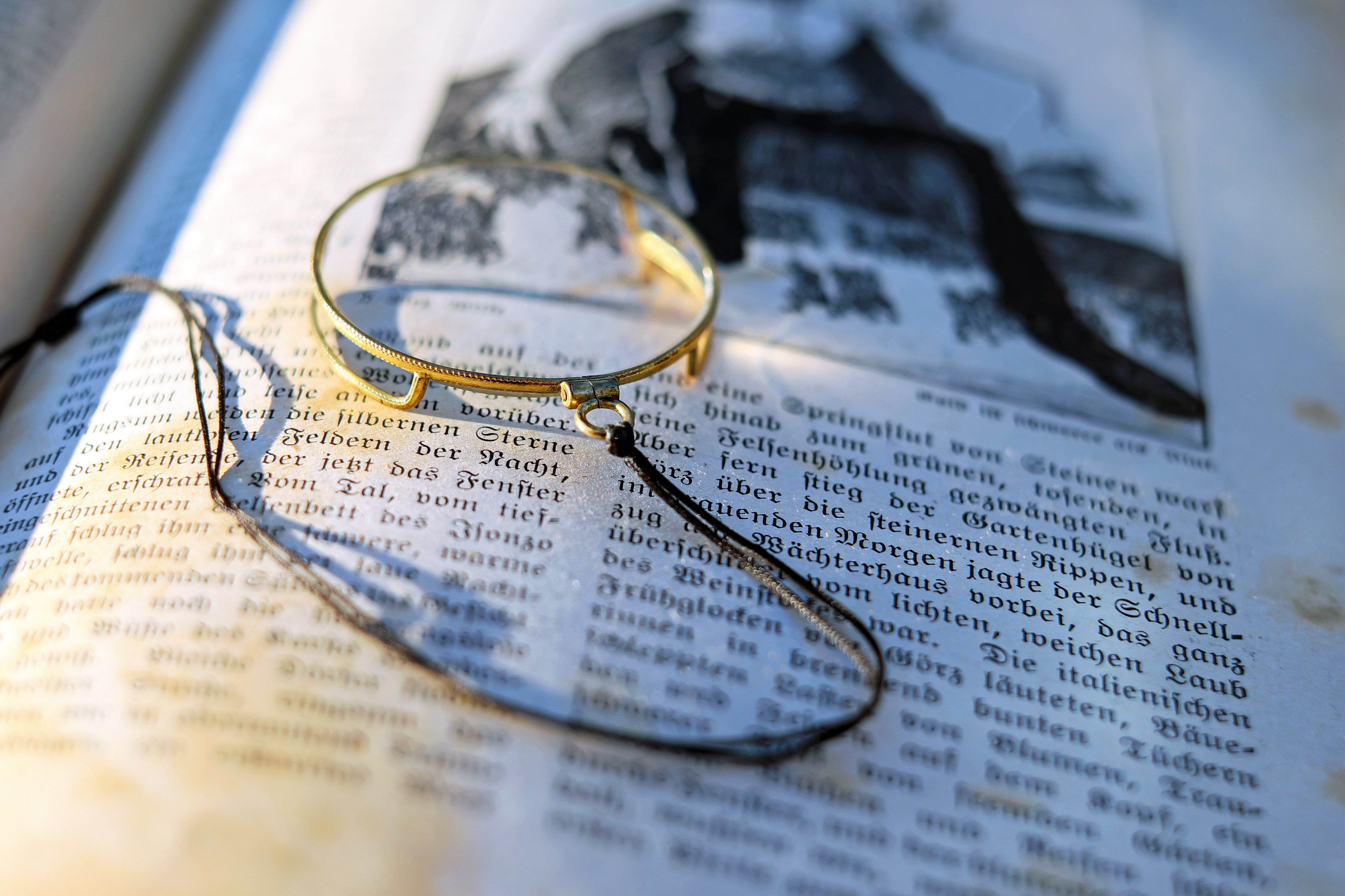 Close-up Photography of Gray Framed Magnifying Glass on Opened Book