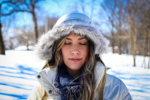 Photo of Woman With Her Eyes Closed in Fur Hooded Coat During Winter