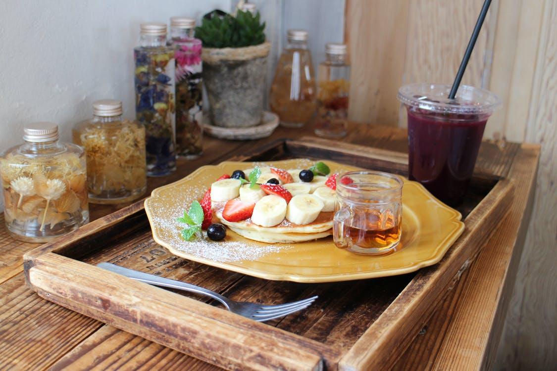 Pancakes garnished with fruits next to a Cup of juice