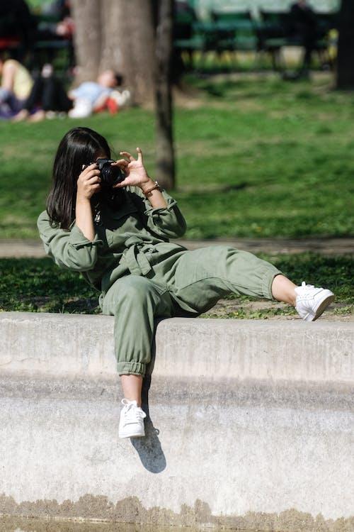 Безкоштовне стокове фото на тему «жінка, камера, повсякденний одяг, сидіння»
