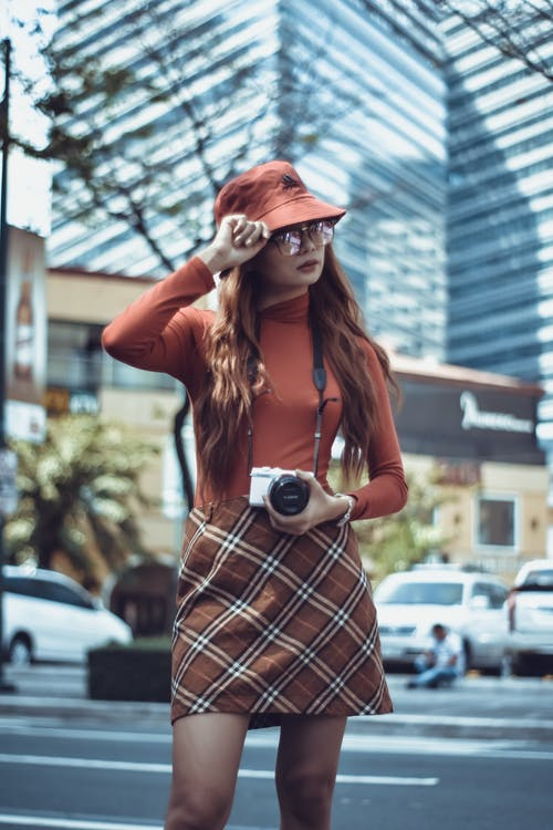 Woman Holding Her Hat While Holding Her Camera