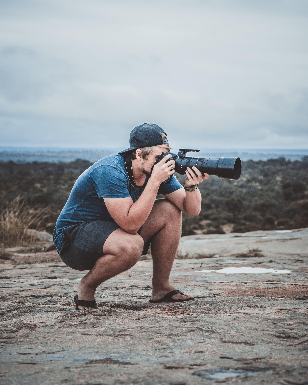 Man Taking Photo Using Black Dslr Camera