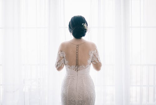Woman Wearing White Lace Wedding Dress Near White Curtain
