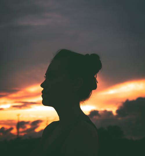 Side view of unrecognizable calm female with bunch hairstyle relaxing on street and admiring picturesque sunset sky