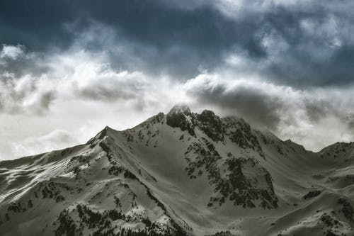 Photo of Snow Capped Mountain Under Cloudy Sky