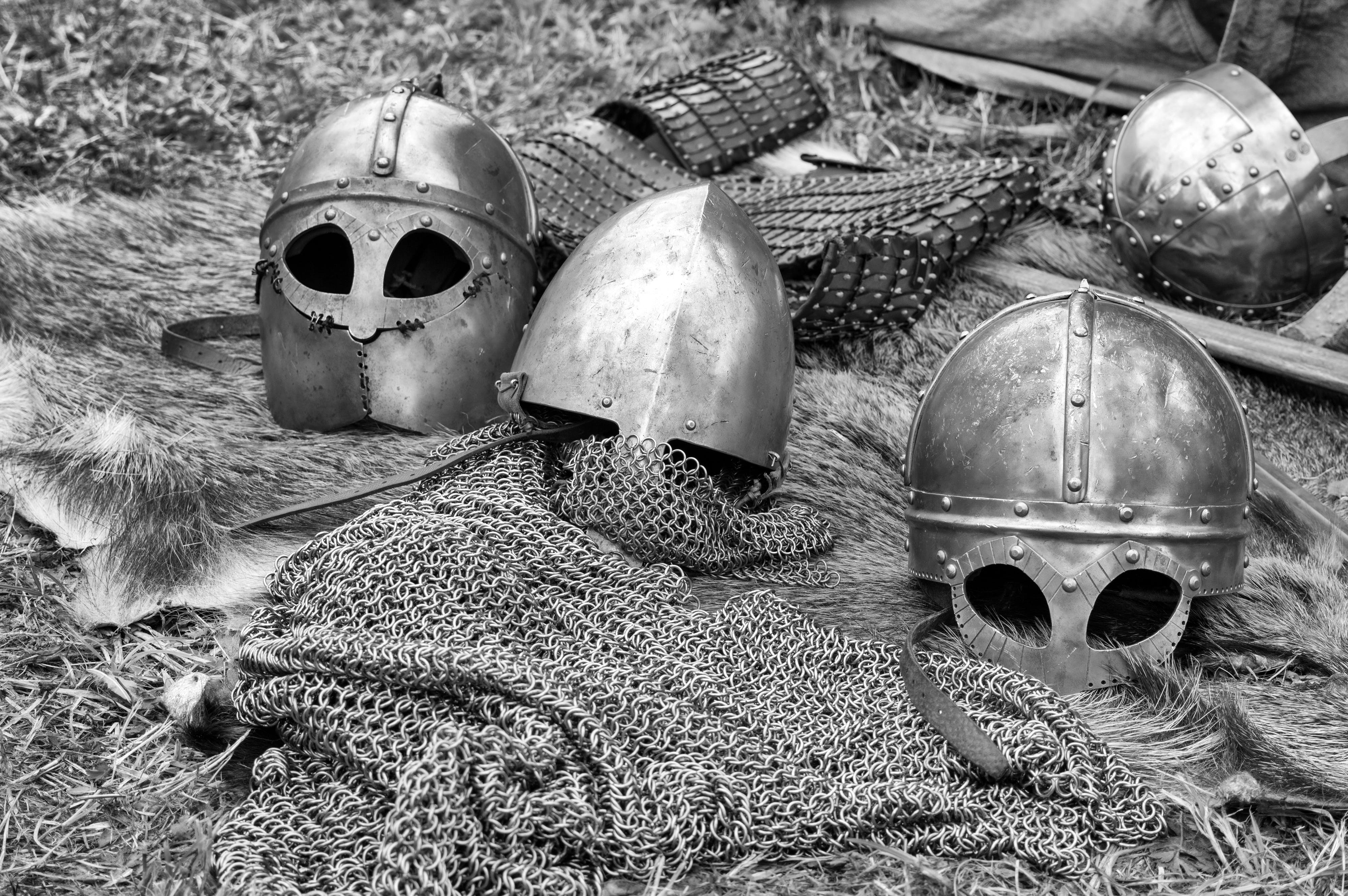 Grayscale Photography of Chainmails and Helmets on Ground