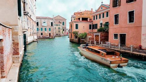 Orange Powerboat Between Medium Rise Buildings