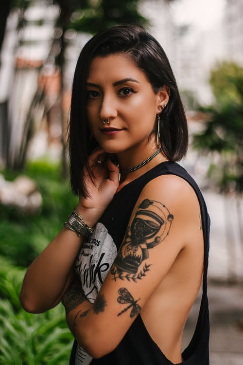 Photo of Woman Wearing Sleeveless Top With Tattoos and Piercings