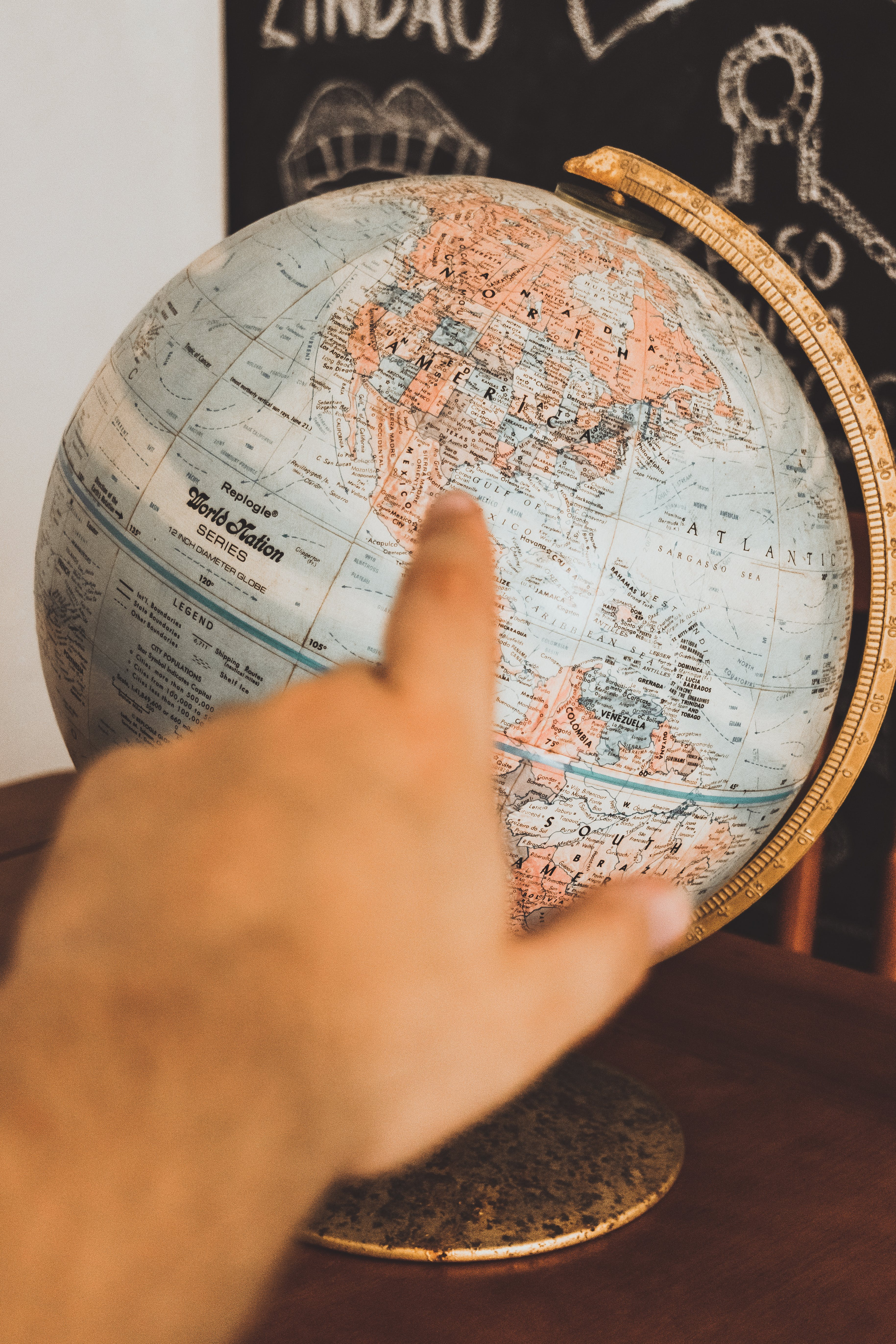 Photo of Person Pointing at Globe