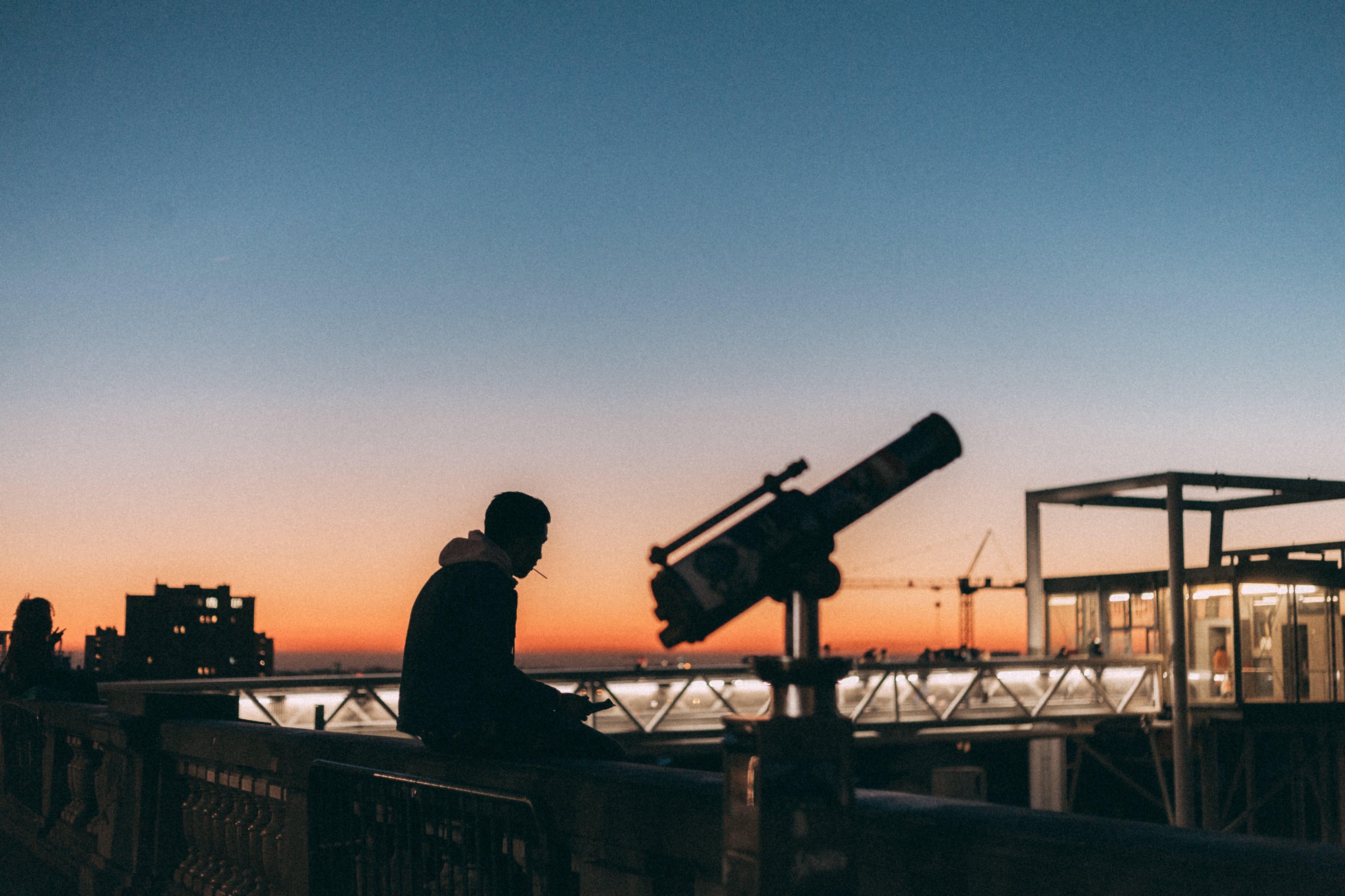 Photo of Man Sitting on Ledge Near Telescope