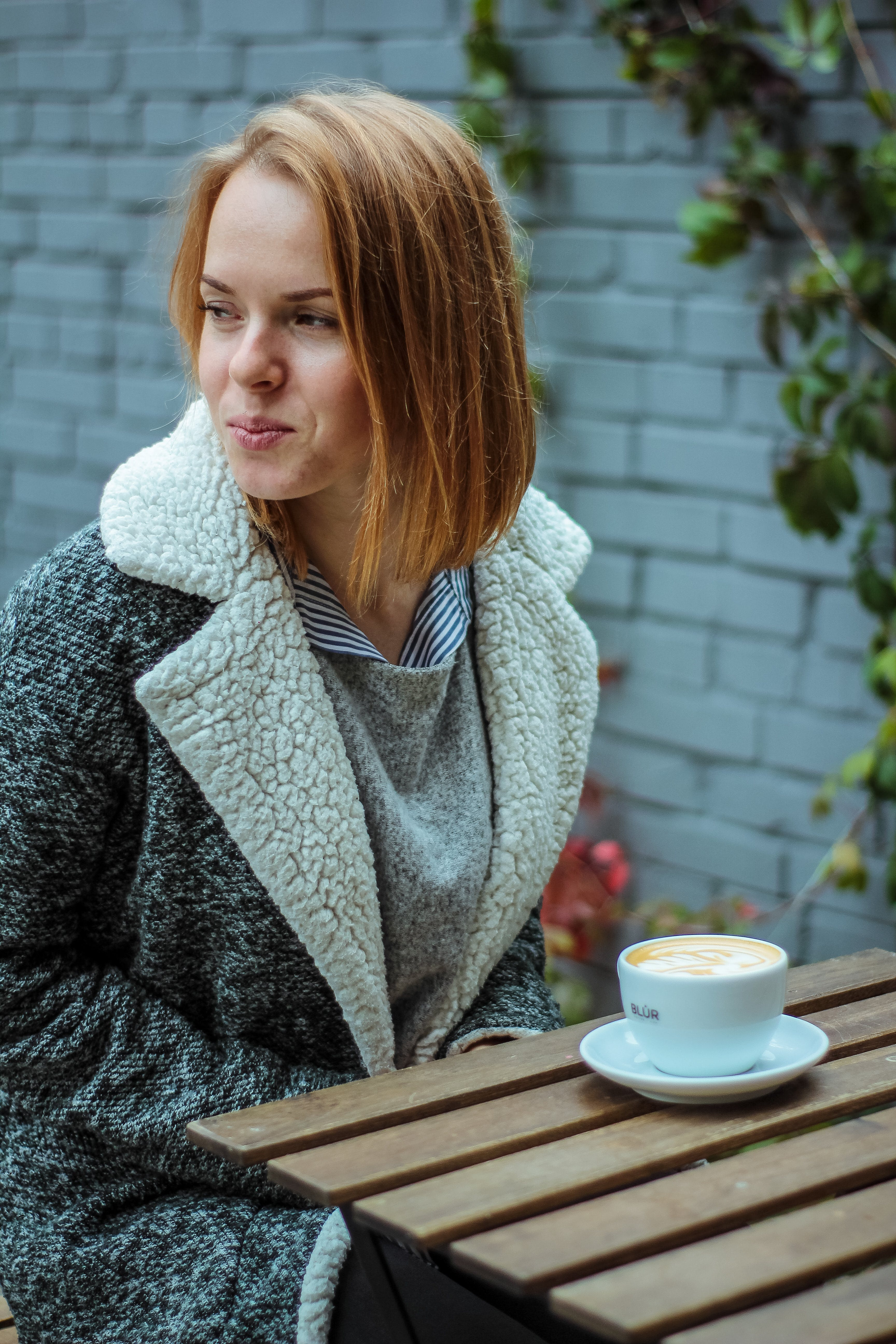 Woman Wearing Gray Coat in Front of Brown Table With White Coffee Cup