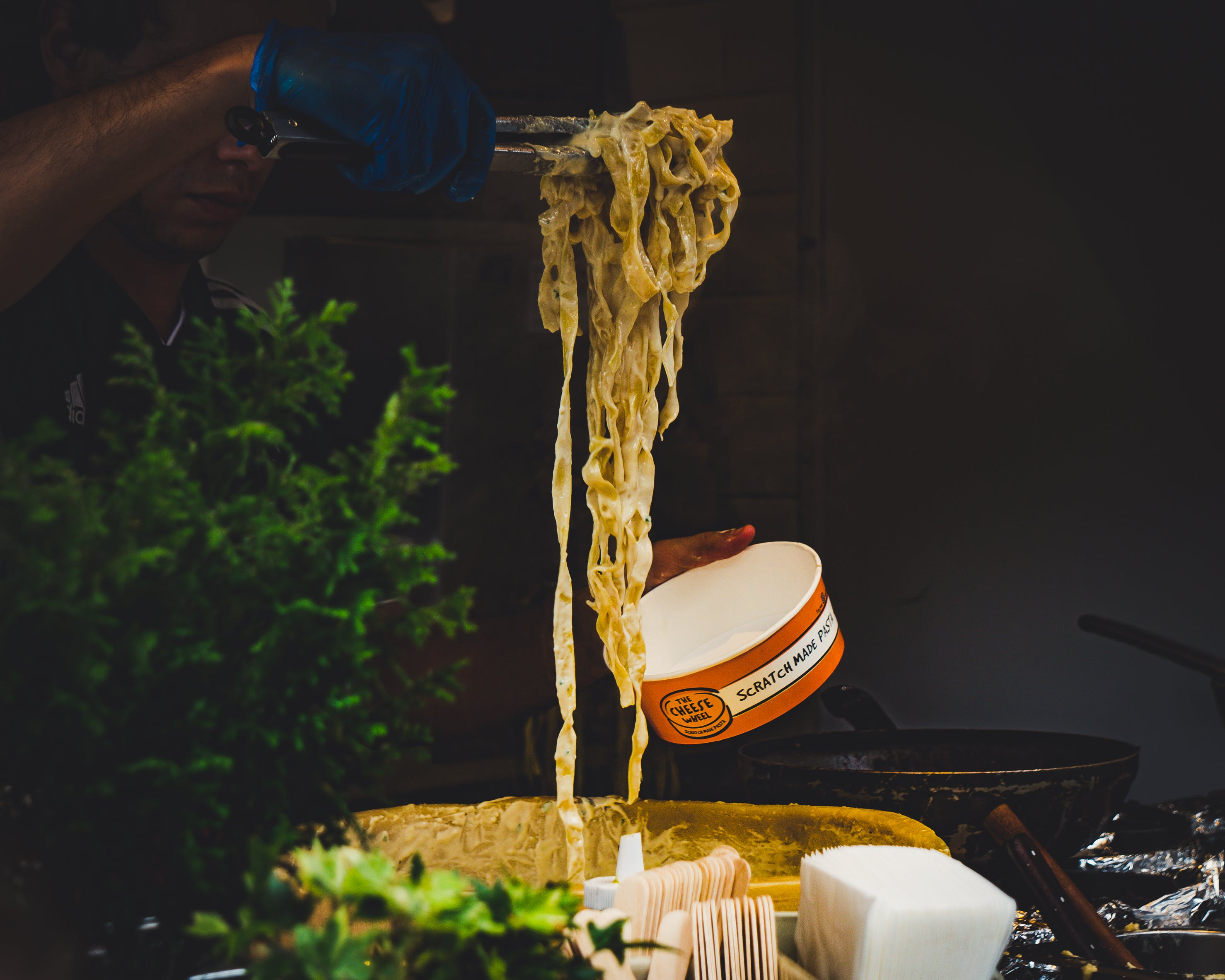 Man Serving Pasta on a Paper Cup