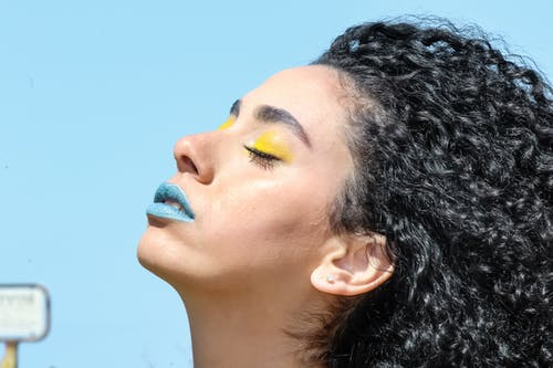 Woman With Yellow Eye Shadow and Blue Lipsticks With Eyes Closed Chin Up